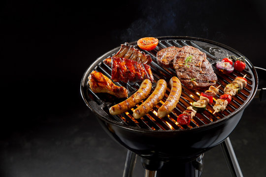Assortment of marinated meat grilling on a BBQ