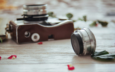 Retro camera roll photo film and flowers on white wooden background
