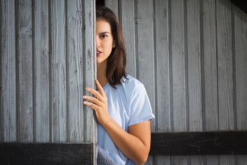Young beautiful farm girl hiding behind barn door