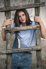 Portrait of pretty young woman holding rustic wooden ladder