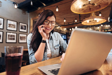 Positive delighted young woman looking at laptop
