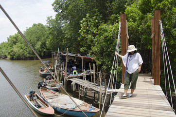 Traveler thai woman walking on wooden bridge for across river at fishing village