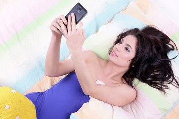 Beautyfull woman never alone with her smartphone in her bed!