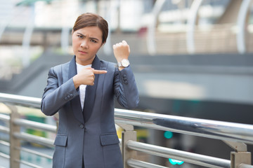 Angry businesswoman check her watch