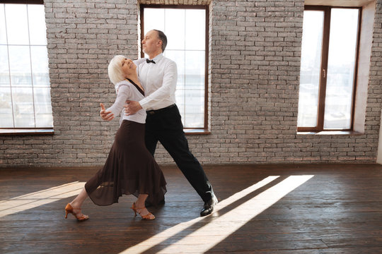 Harmonious senior dance couple dancing tango at the ballroom