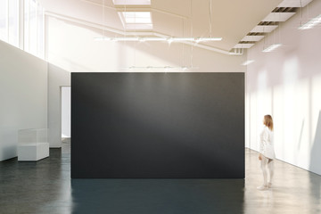 Woman stand near blank black wall mockup in modern white gallery. Girl walk near dark big stand mock up in museum with contemporary art exhibitions. Large hall interior, grey banner exposition