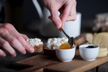 Man's hand putting jam on bread with ricotta cheese