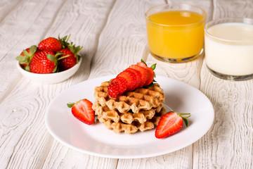 Waffels with strawberry, orange juice and milk