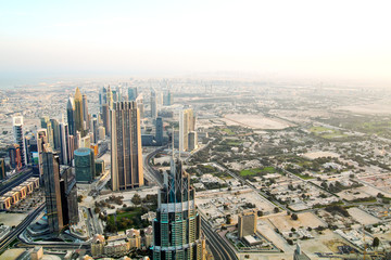 Aerial view of downtown Dubai with buildings skyscrapers and a dusty skyline at sunrise.