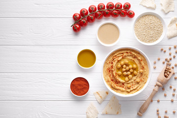Hummus traditional arabic healthy vegan dip chickpeas paste snack flat lay with natural ingridients, tahini, paprika, olive oil, pitta bread on white table. Healthy vegetarian nutrition food