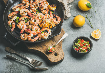 Seafood dinner. Grilled tiger prawns in cast iron grilling pan with lemon, leek, chili pepper and mint salsa sauce over grey concrete background, selective focus. Slow food concept