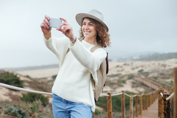 Smiling woman with hat and backpack taking photo with her smartphone, traveling among natural sand meadows