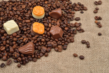 Jute background. Assortment of dark, white and milk chocolate stack on roasted  coffee beans. Sweet and rustic image. Selective macro focus. Chocolates background. Sweets