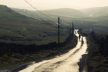 Cyclist rides along a sunlit wet moorland country lane in North Yorkshire, UK.