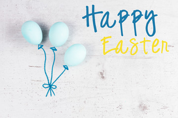 Row of blue eggs on aged wooden table desktop with happy easter greeting