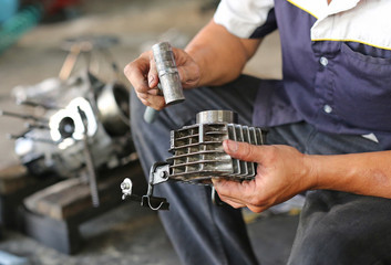 mechanic fixing motocycle engine
