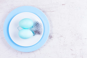 Plates with two painted blue eggs and feather on white wooden tabletop