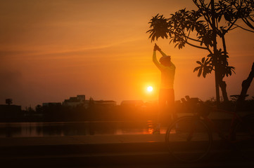 Man exercise in park near lake at sunset/ sunrise,soft focus,silhouette style.