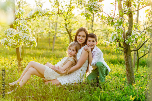 Beautiful young family in a blooming spring garden.