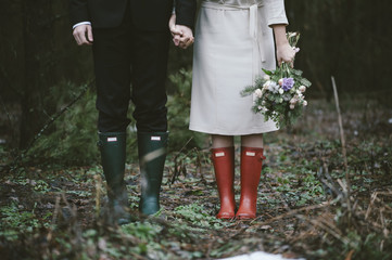 Wedding couple standing in the forest wearing colorful rubber boots