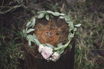 Wedding rings inside a flower headband on a wooden stump