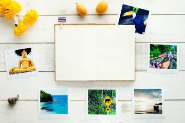 Thai background. Memories of Thailand / travel planning. Tourist photos, marigold garland, exotic fruits, open notebook.