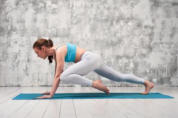 Girl wearing colorful sportswear practicing yoga.