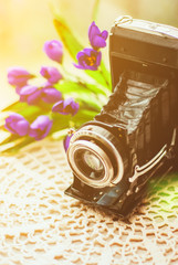 Old Vintage Camera with Beautiful Bouquet of Flowers on knitted tablecloth. Old Vintage still life Concept.