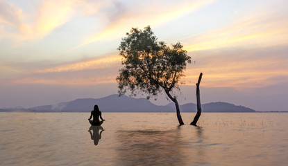 Silhouette of woman sitting on the lake during a beautiful sunset, with reflection in the water...