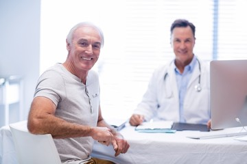 Portrait of smiling doctor and senior man