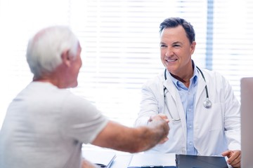 Doctor shaking hands with senior man