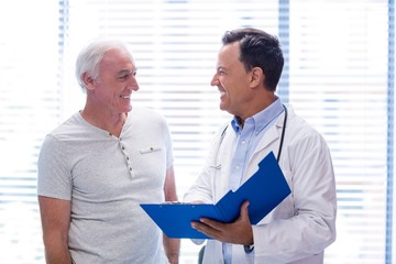 Doctor and senior man smiling while having discussion on file