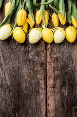 Easter eggs on wooden background. Spring concept on plank. Yellow eggs with nature decoration.