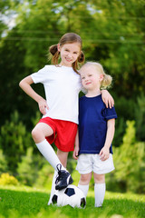 Two cute little sisters having fun playing a soccer game on sunny summer day. Sport activities for children.