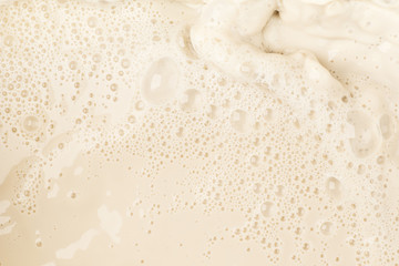 Soy milk splash and bubble foam on top view food and drink background close up