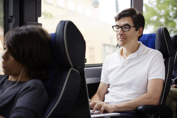 Mature man using laptop in bus and boy on foreground (12-13)