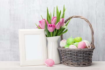 Easter eggs, photo frame and pink tulips