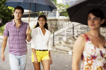 Woman, man and girl (16-17) walking together with umbrellas