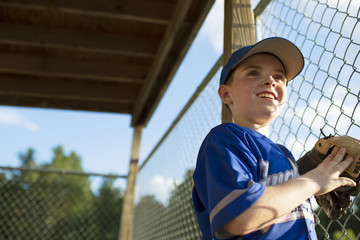 Young baseball players leaning against chain link fence