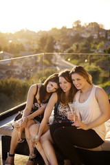 Smiling women relaxing with drinks on patio