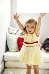 Smiling little girl with arms raised