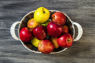 Basket in red apples, basket full of apples, apples pictures on authentic wood floor,