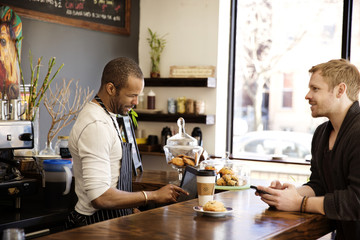 Customer buying coffee while talking to owner at counter in cafe