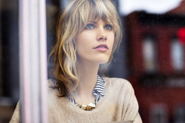 Young woman looking through window in cafe