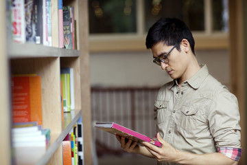 Man holding book standing by library shelf