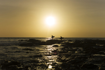 Surfers walk on rocks on the Pacific ocean as they surf during sunset in Tamarindo, Costa Rica.