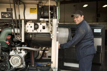 Portrait of mechanic repairing engine