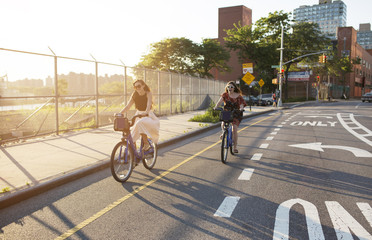 Young women riding bicycle on street