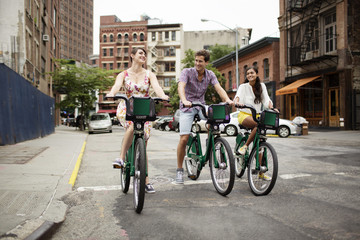Woman, man and teenager (16-17) cycling in city