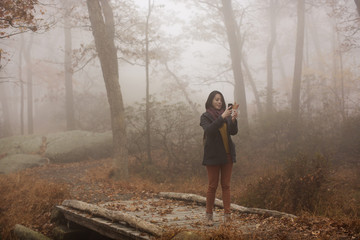 Young woman taking pictures of forest